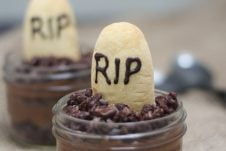 A close up of a Halloween graveyard mousse with an edible gravestone saying RIP in chocolate with a second one in the background.
