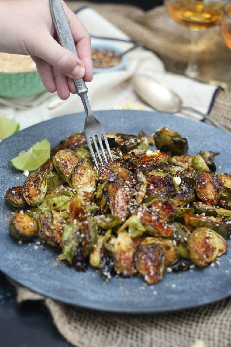 image of a hand holding a silver fork reaching into sweet chilli flavoured brussels sprouts on a grey plate topped with cereal and nut mixture and a wedge of lime