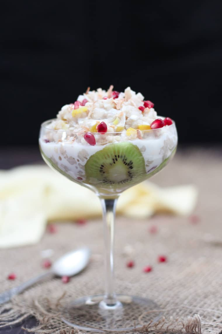 A glass with mango kiwi vegan coconut rice pudding.