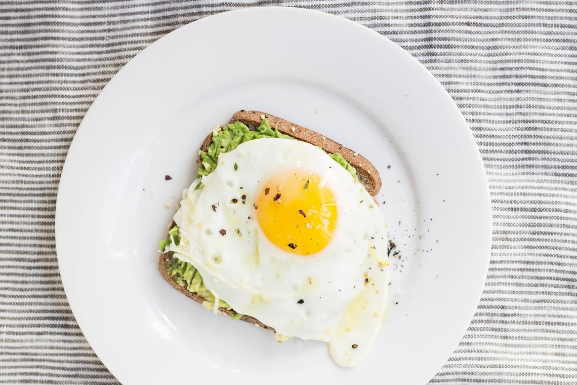 birds eye view of an egg on top of avocado toast on a white plate