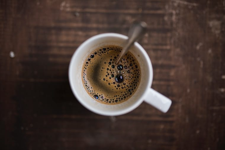 Birds eye view of coffee in a mug with a stir spoon as a cause for stomach cramps.
