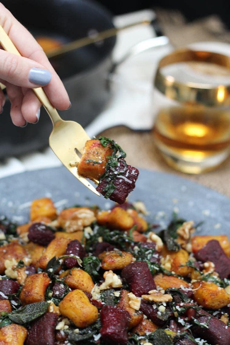 Fork digging into a platter of gnocchi.