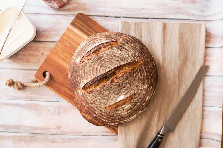 Loaf of bread on cutting board.