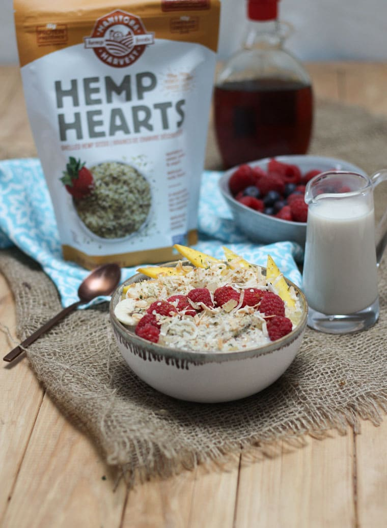 A bowl of no oats porridge with a bag of hemp hearts in the back.