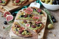 Vegan Olive Pesto Flatbread with Olives from Spain, Roasted Grapes and Figs This Vegan Olive Pesto Flatbread with Olives from Spain, Roasted Grapes and Figs is a perfect plant-based healthy holiday appetizer to feed a crowd! Serves 16 Gordal olives from Spain Pesto 1/2 cup pistachios (shelled) 1 cup pitted Gordal olives from Spain 1 garlic clove, minced 1 cup arugula ¼ cup extra virgin olive oil Pepper, to taste Flatbread 3 tbsp extra virgin olive oil, divided ½ onion, thinly sliced 1 ½ cups red grapes 2 sprigs rosemary 6 small whole grain naan breads 4 figs, thinly sliced ¼ cup pitted Dark Hojiblanca olives from Spain, thinly sliced ¼ cup crushed pistachios In a food processor, puree the pistachios until they reach a powder like consistency, then add in the Gordal olives from Spain, garlic, arugula and oil. Season with pepper, to taste. Set aside. Preheat oven to 450 F. Heat a tablespoon of oil in a nonstick skillet over medium-low heat. Add in the onions and saute until dark and caramelized, about 50 minutes. Set aside. Meanwhile, place the grapes and rosemary on a baking sheet and drizzle with a tablespoon of oil. Place the naans on baking sheets and drizzle with the remaining tablespoon of oil. Roast the grapes for 20-25 minutes or until caramelized, and the flatbread for 5-10 minutes just until toasted around the edges. When ready to serve, smear the olive pesto all along the toasted naans. Top with the roasted grapes, figs, Dark Hojiblanca olives from Spain, caramelized onions and pistachios. Enjoy!