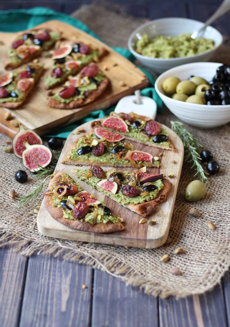 vegan pesto and olive flatbread garnished with roasted grapes and figs