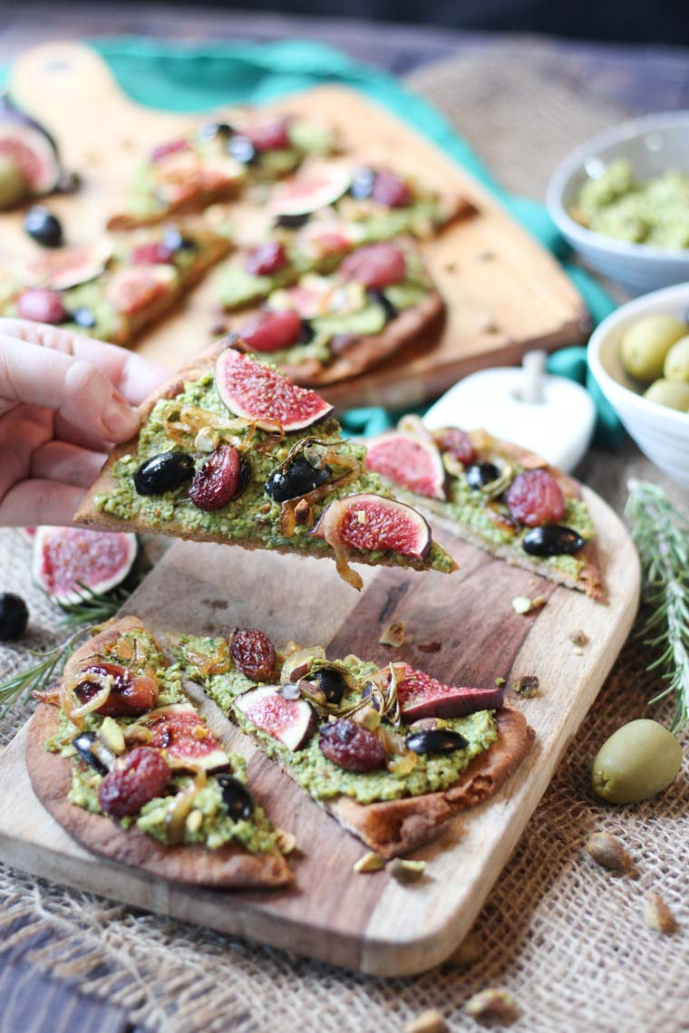 hand taking a slice of vegan olive and pesto flatbread from a wooden surface