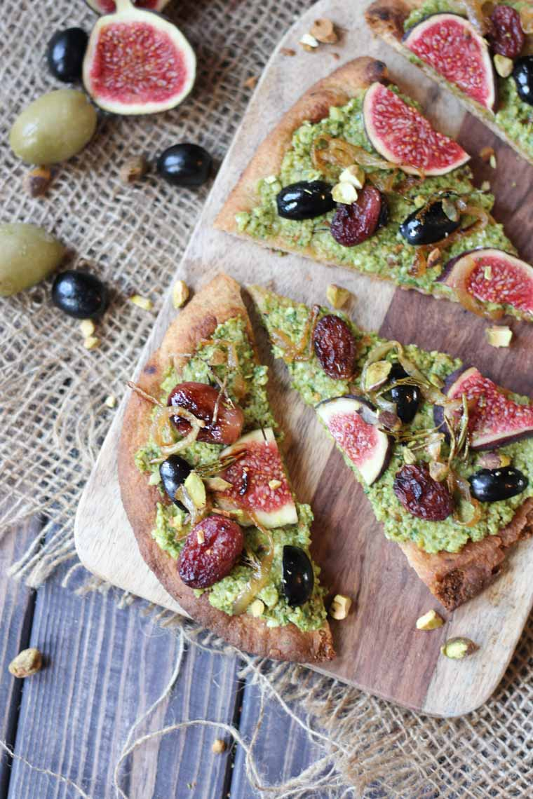 birds eye view of vegan pesto and olive flatbread on a wooden serving board topped with figs and roasted grapes