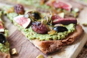 close up of flatbread with vegan pesto, olives, and grapes on a wooden surface
