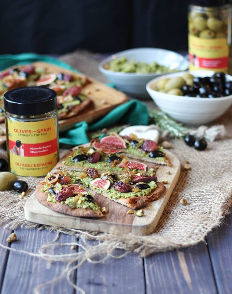 vegan pesto flatbread on a wooden serving board next jars of ilves