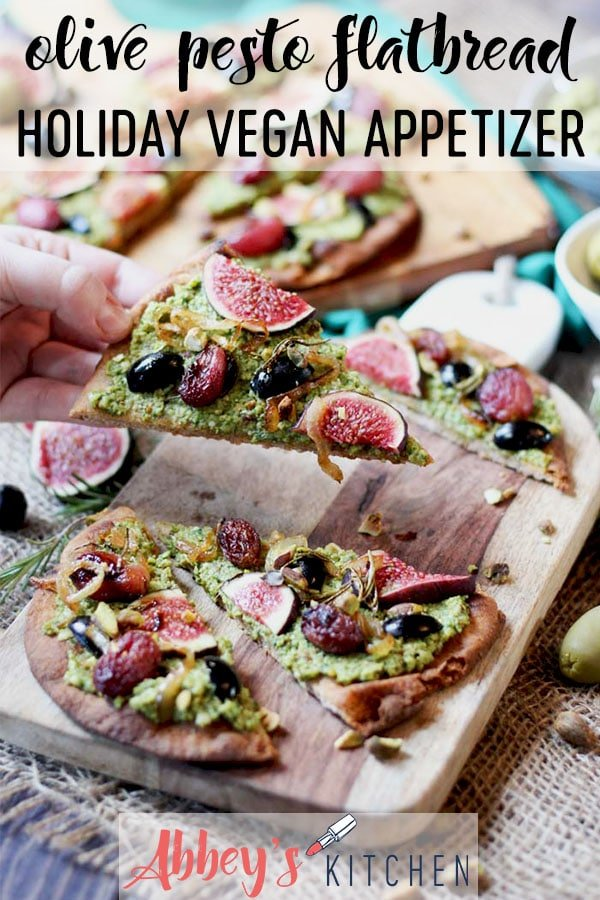pinterest image of vegan flatbread with pesto, olives, and figs on a wooden surface with text overlay