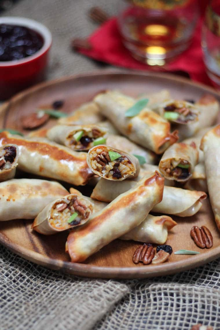 Wooden platter containing baked spring rolls.