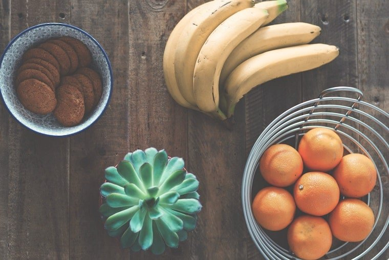 Oranges in a bowl, bananas, and cookies in a bowl on a counter top to increase electrolytes to help relieve stomach cramps.