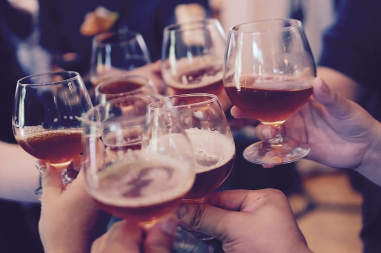 """Several hands holding up glasses of beer to """"cheers."""