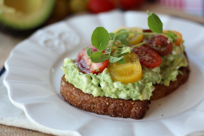 high protein avocado smash on toast garnished with tomatoes and greens on a white plate