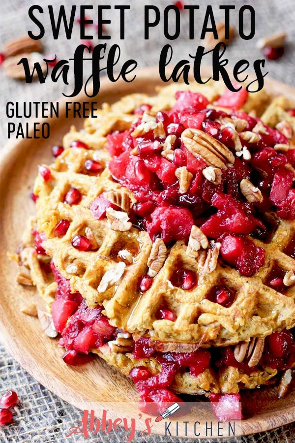 pinterest image of sweet potato waffle latkes topped with cranberry compote and nuts on a wooden plate with text overlay
