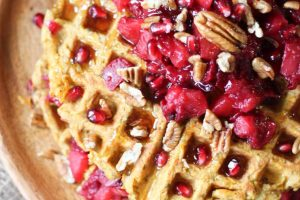 close up image of sweet potato waffle latkes garnished with cranberry compote and pecans