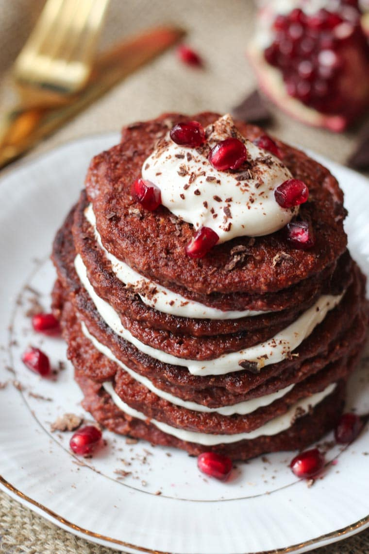 Stack of pancakes topped with pomegranate seeds