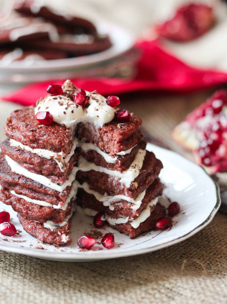 Stacked red velvet pancakes topped with pomegranate seeds