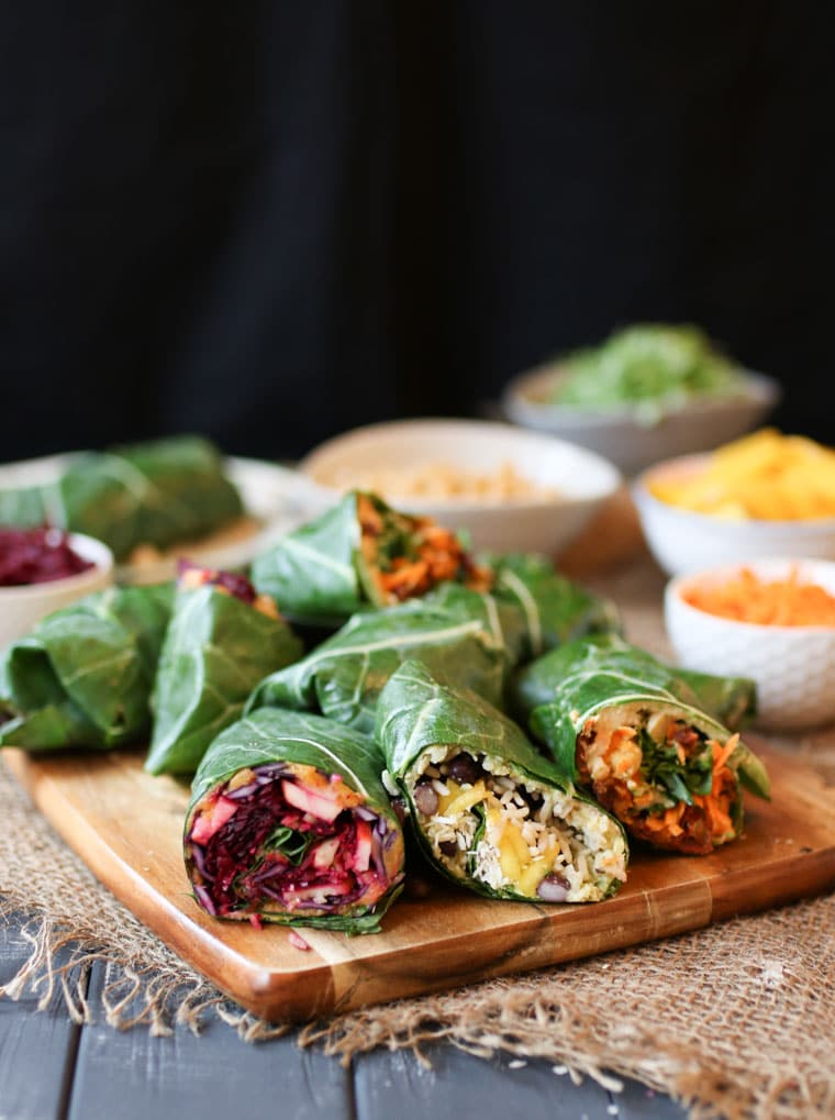 three vegan collard green wraps with assorted fillings served on a wooden platter with additional collard wraps and bowls of vegetables in the background