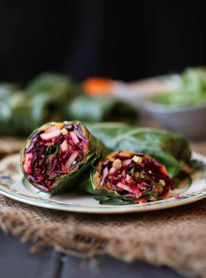 close up image of vegan sweet potato and apple collard green wrap on a white plate