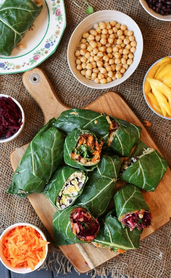 birds eye view of various vegan collard green wraps on a wooden serving board