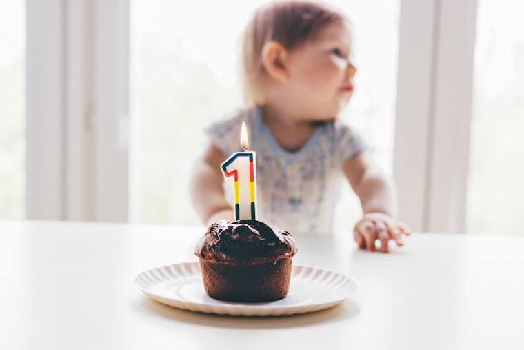 cupcake with a first birthday candle in front of a toddler