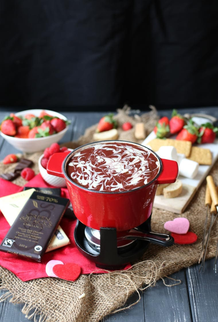 fondue with a variety of foods for dipping in the background