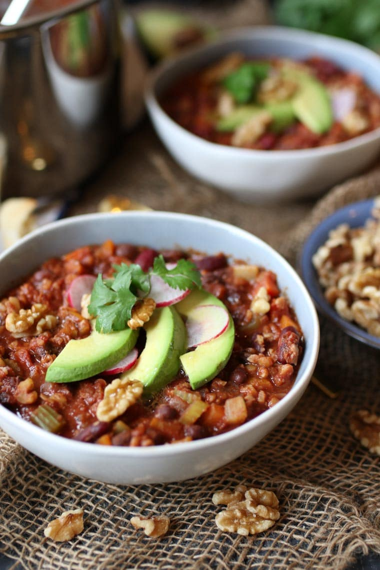 Chili in a bowl topped with avocado.