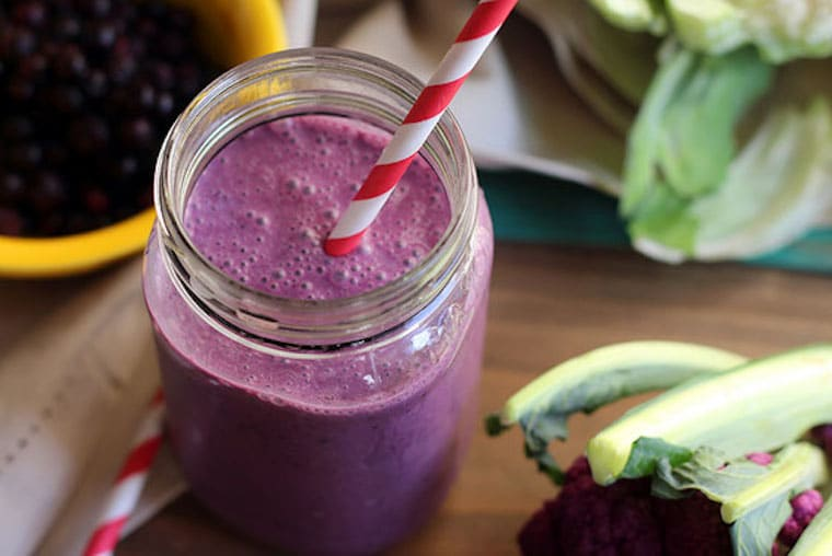 close up of vegan and gluten free wild blueberry and cauliflower smoothie served in a clear jar with a red and white straw with fresh fruit and cauliflower in the background