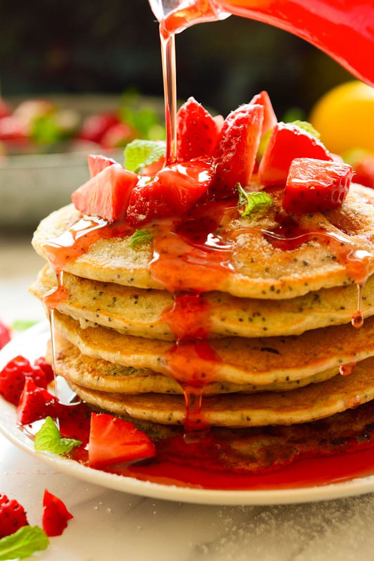 close up of a stack of strawberry lemon poppyseed pancakes for easter brunch garnished with strawberry sauce and chopped fresh strawberries