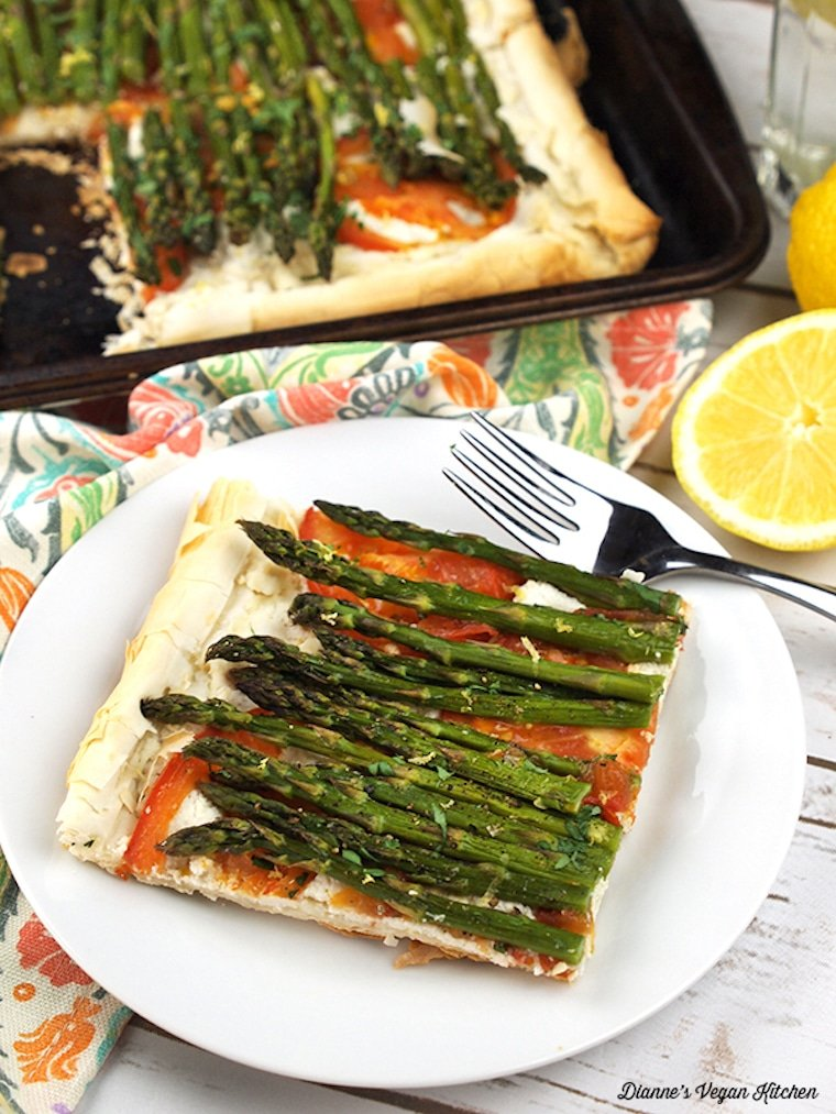 slice of vegan asparagus and tomato tart with cashew ricotta on a white plate with a silver spoon with the rest of the tart on a black baking tray in the background and fresh lemon wedges on the side