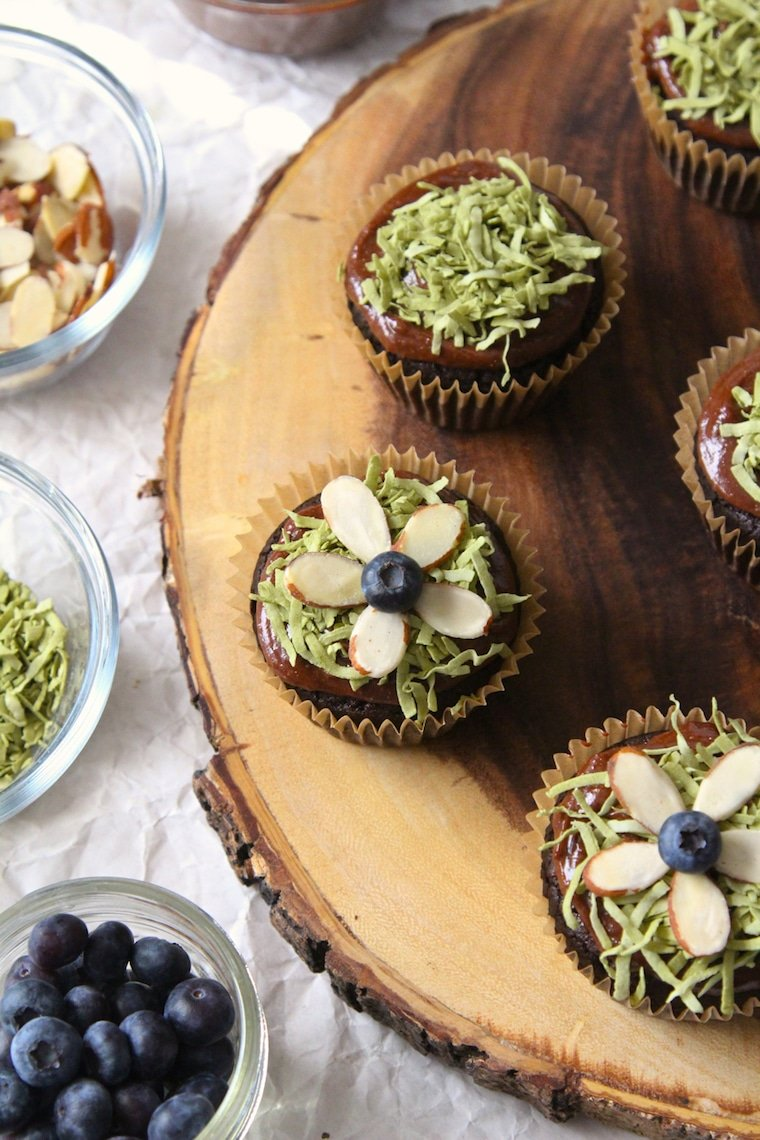 birds eye view of vegan chocolate easter cupcakes garnished with almonds and blueberries on a wooden serving board next to clear bowls with additional garnished inside