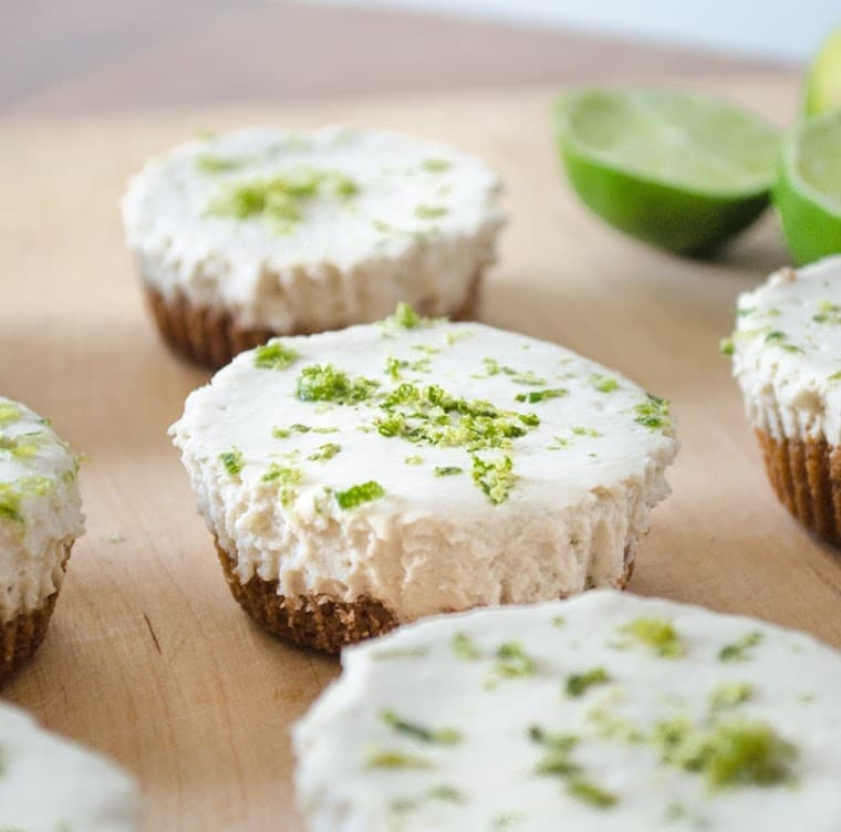 close up shot of vegan mini key lime pies garnished with lime zest on a wooden serving platter
