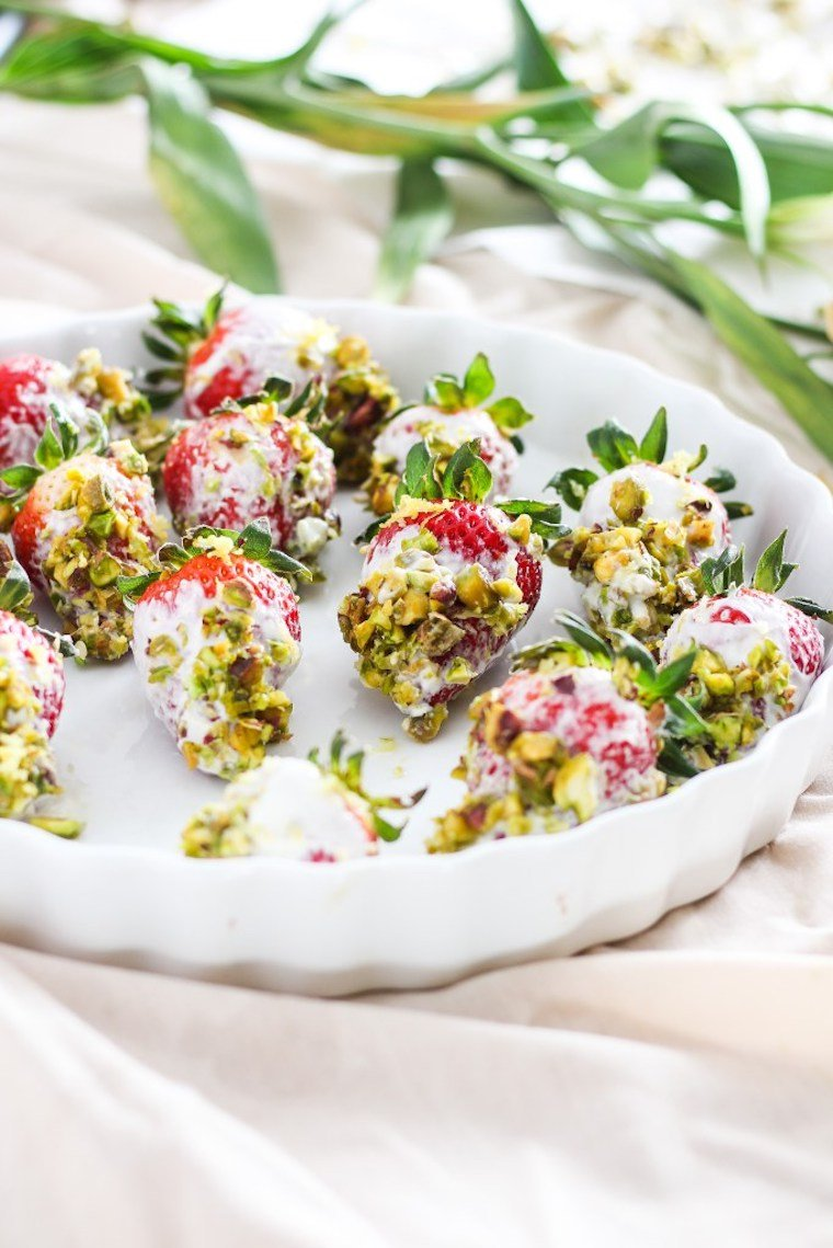 white serving plate with multiple vegan pistachio yogurt dipped strawberries