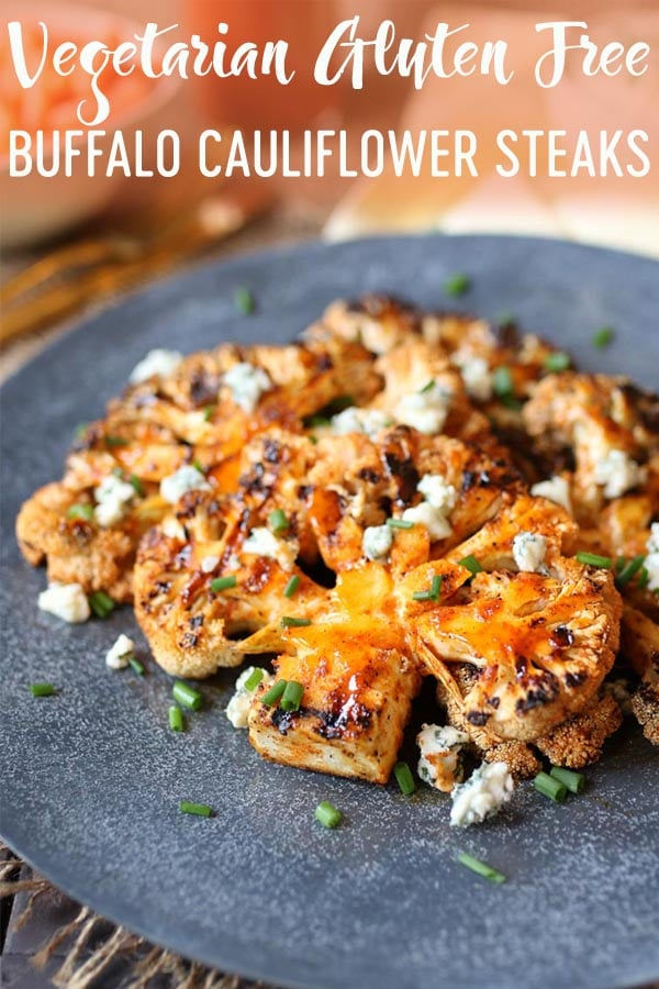 Buffalo cauliflower steaks on a grey plate topped with blue cheese and chives.