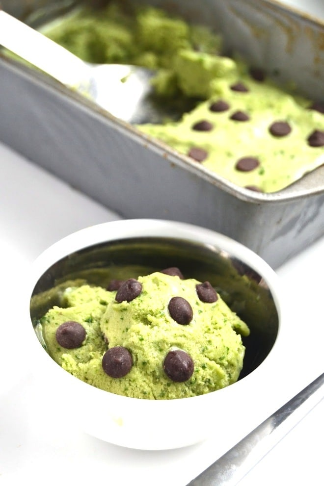 close up of vegan mint chocolate chip protein ice cream garnished with additional chocolate chips served in a white bowl with additional ice cream in a grey tray in the background