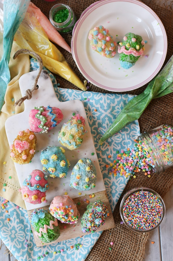 Overhead view of eight Vegan Gluten Free Rice Krispies Easter Eggs coated in a Homemade Vegan White Chocolate with sprinkles and candies on top on a serving board on top of a festive tablecloth