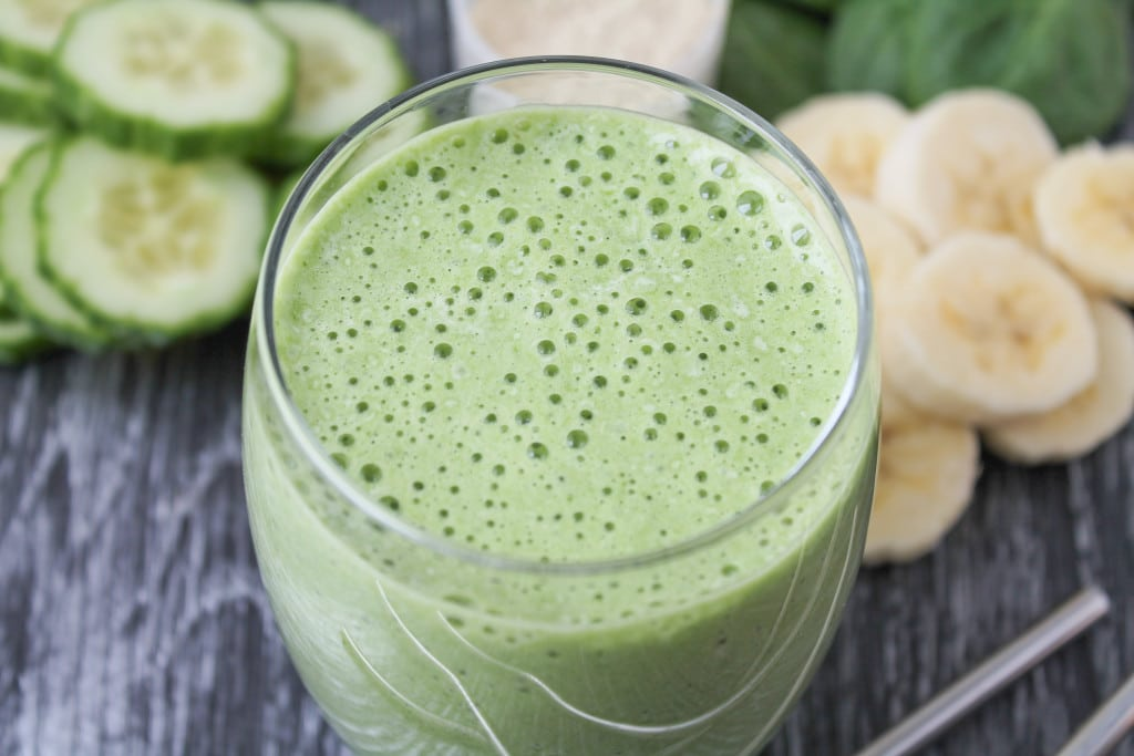 close up image of vegan green st. patrick's day shamrock shake in a clear glass with banana and cucumber slices in the background