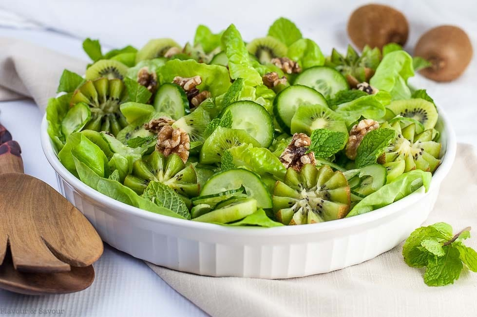 close up of kiwi cucumber salad with walnuts and fresh mint served in a large white dish with wooden serving utensils