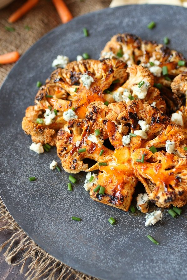 Buffalo cauliflower steak on a grey serving plate topped with blue cheese and chives.