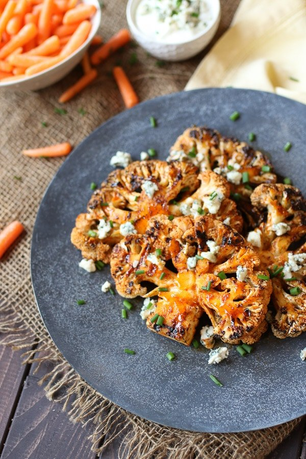 Buffalo cauliflower steaks on a grey serving plate topped with blue cheese and chives next to a bowl of carrots.