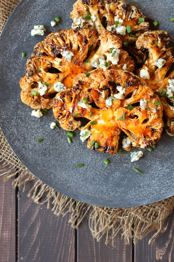 Buffalo cauliflower steaks topped with blue cheese and chives on a grey serving platter.