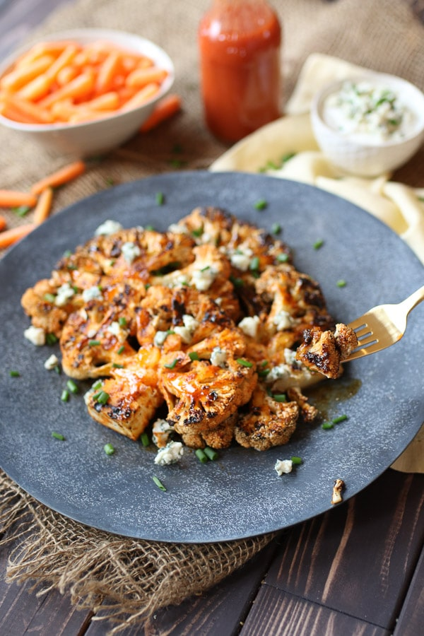 Gold fork digging into buffalo cauliflower steaks.
