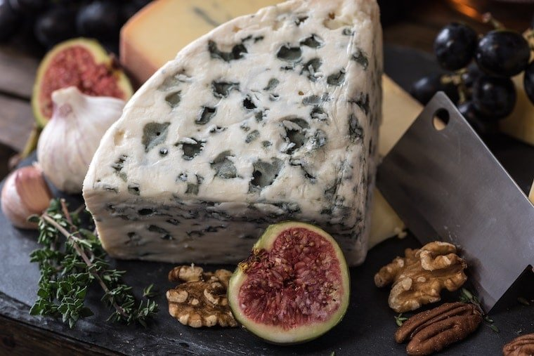 Plate of blue cheese, figs, walnuts, pecans and others foods that are not allowed for pregnancy food safety.