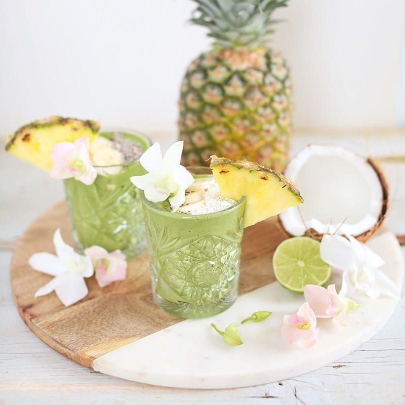 two small clear glasses filled with vegan green tropical smoothies garnished with slices of pineapple with additional pineapple and lime in the background