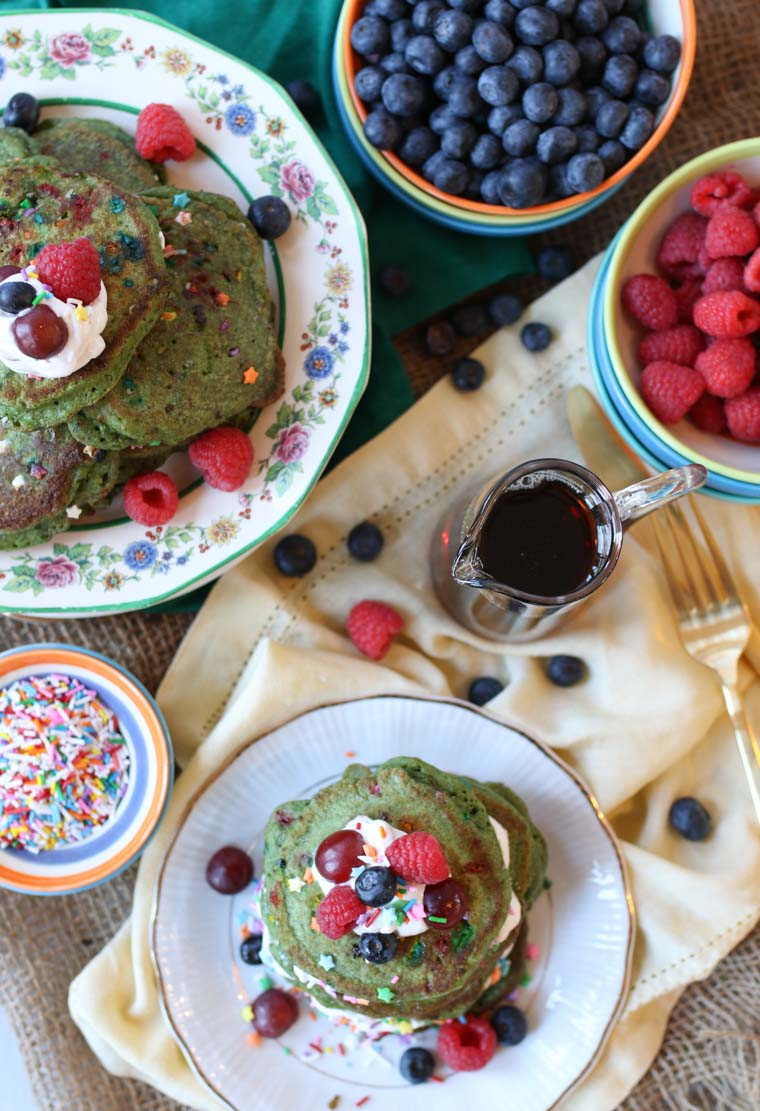 A pile of matcha protein pancakes on a plate next to bowls of blueberries and raspberries.