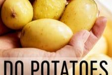 Two hands holding yellow flesh potatoes under running water.