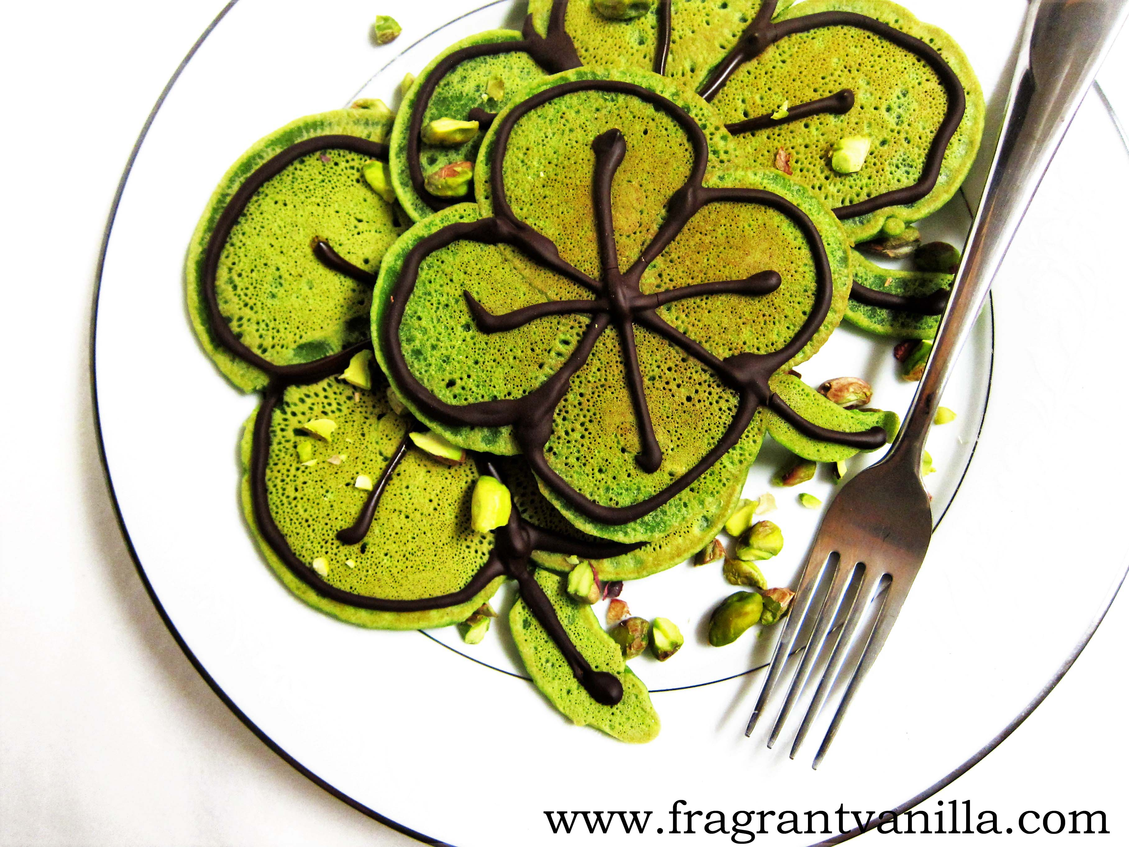 birds eye view of vegan st. patrick's day green shamrock pancakes served on a white plate with a silver fork garnished with chopped pistachios
