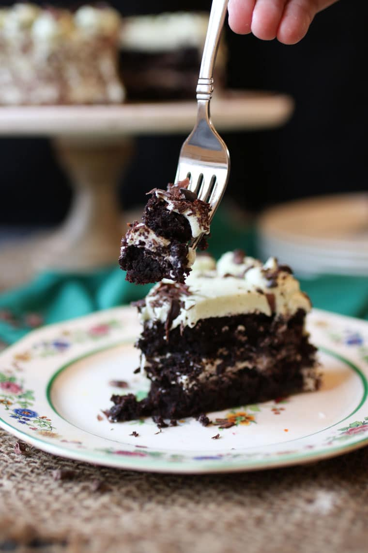 A slice of chocolate cake with a piece on a fork.